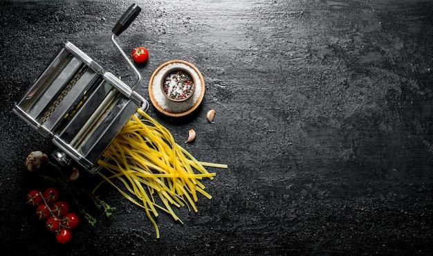 Macchina per la cottura della pasta fatta in casa con spezie e pomodoro. sul nero rustico