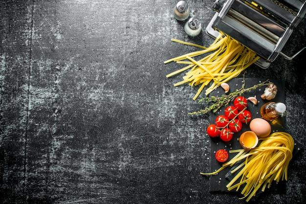 Macchina per fare pasta fatta in casa e pasta cruda con pomodoro e olio. su fondo rustico