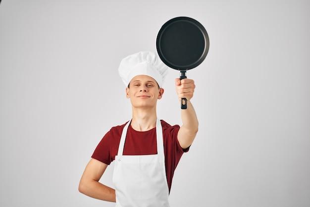 Padella professionale a macchina nel lavoro in cucina delle mani