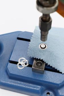 Macchina per rivetti e bottoni nella produzione di cucito