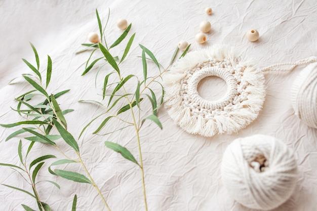 Decoro in cotone macramè. materiali naturali: filo di cotone, perline di legno. decorazioni ecologiche, ornamenti, decorazioni fatte a mano. copia spazio