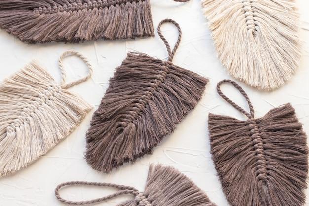 Foglie di piume di macramè fatte di filato di corda di cotone in colore marrone e naturale su sfondo bianco. fatto a mano, hobby creativo. vista dall'alto, piatto.