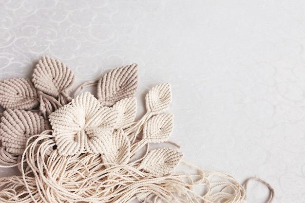 Fiori di macramè e bastone di legno su sfondo bianco