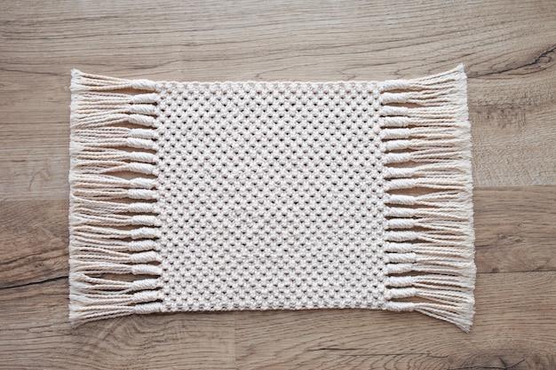 Tappeto macramè su tavolo in legno o moquette sul pavimento. sfondo macrame beige fatto a mano. texture macramè, lavorazione a maglia ecologica e moderna.