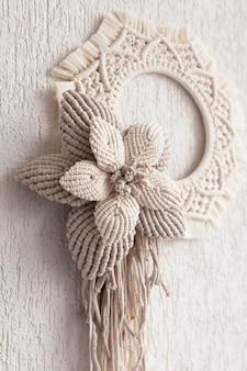 Ghirlanda di macramè con grande fiore di cotone su una parete in gesso decorativo bianco