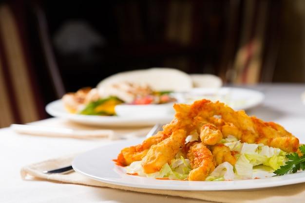 Macro piatto principale appetitoso della carne di pesce sulla tavola durante la cena.