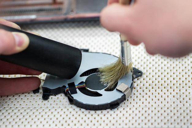 Macro di una spazzola che pulisce un ventilatore del computer portatile
