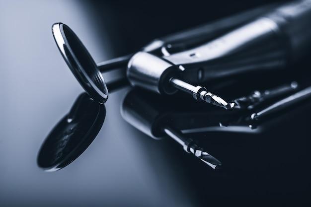 Macro di strumenti metallici lucidi dentali sulla superficie con riflessione