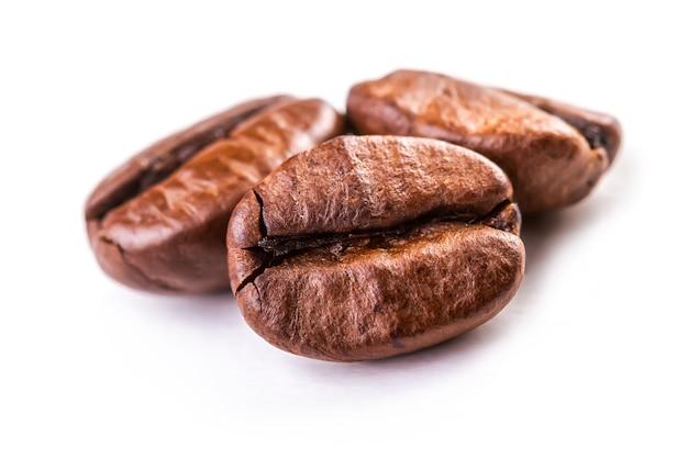 Macro closeup isolato di chicchi di caffè freschi e gustosi pronti da macinare.