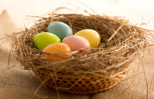 Foto macro di uova di pasqua colorate che giacciono nel nido sul tavolo