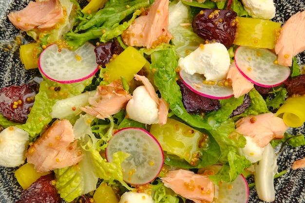 Foto macro di insalata con salmone, ravanello, zucchine e barbabietole su un tavolo di legno