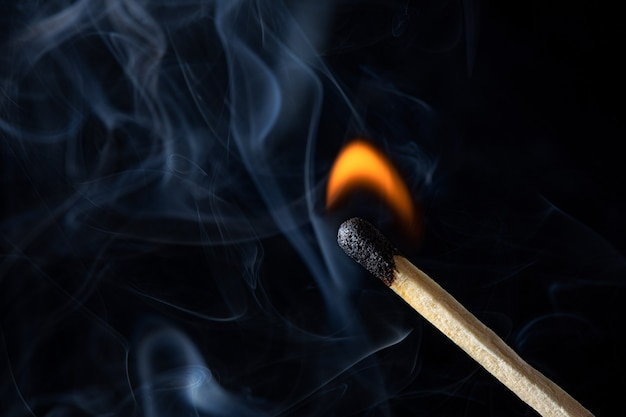 Una fotografia macro di un fiammifero illuminato con un po 'di fumo e fuoco