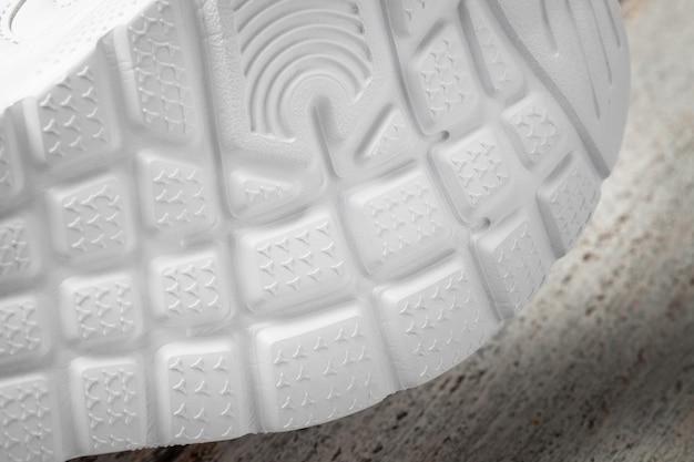 Macrofotografia delle suole di sneakers bianche sneakers sportive per bambini sdraiate su un fianco con ...