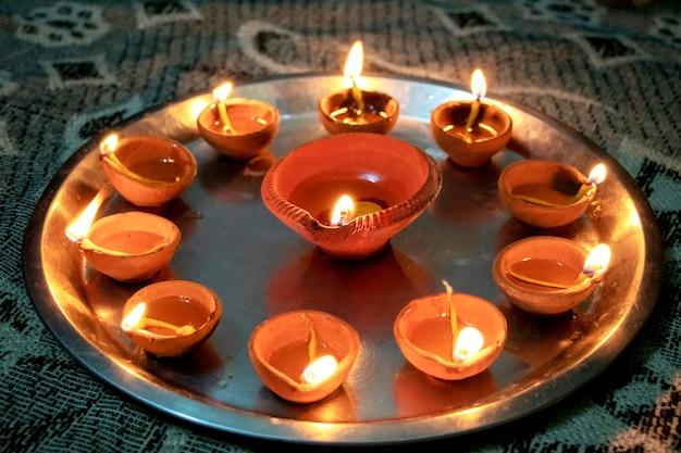 Riprese macro di diyas che vengono accese a mano o con una candela per la festa religiosa indù di diwali. questi colorati vasi di terracotta contengono olio e uno stoppino di cotone per illuminare