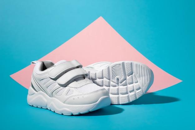 Macro vista laterale una sneaker bianca da ragazza si trova di fronte a una seconda sneaker sdraiata su un fianco con...