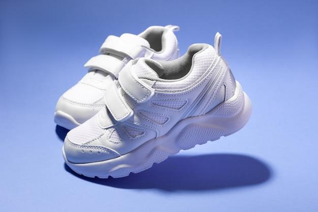 Macro vista laterale due scarpe da corsa per bambini bianchi volanti con velcro isolato su sfondo viola