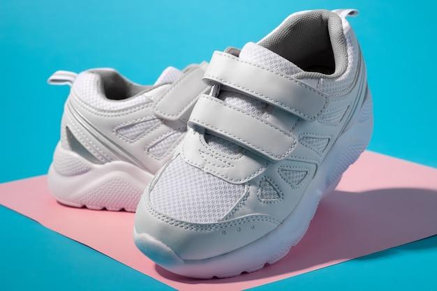 Macro vista laterale di due sneakers bianche per bambini con chiusure in velcro per calzature comode su un geomet...