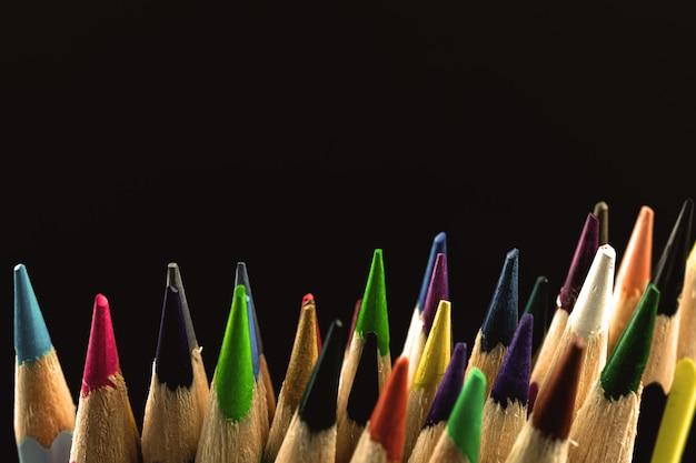 Macro ripresa in studio delle matite da disegno a colori per la creazione, primo piano delle punte affilate, sfondo nero con foto dello spazio della copia