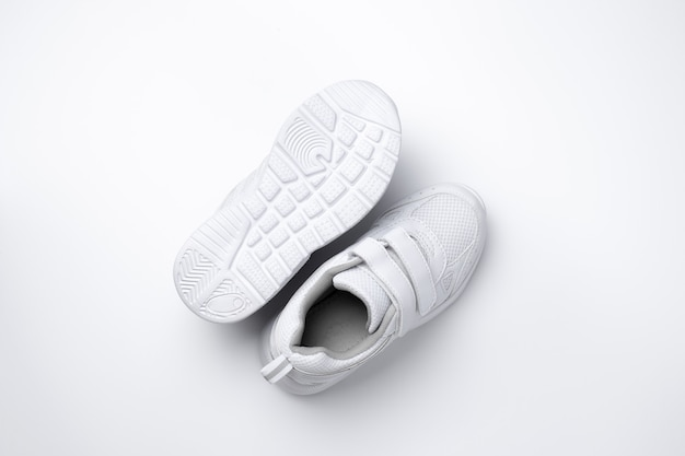 Macro vista dall'alto due scarpe da corsa unisex bianche una scarpa da corsa si trova suola isolata su sfondo bianco...