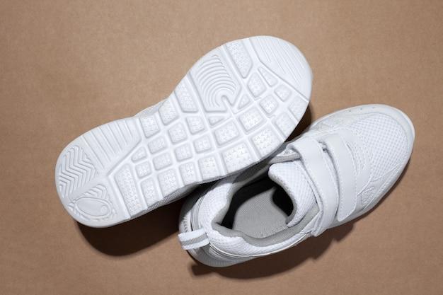 Macro vista dall'alto due scarpe da ginnastica bianche una scarpa da ginnastica si trova sulla suola con ombre dure isolate su una pap...
