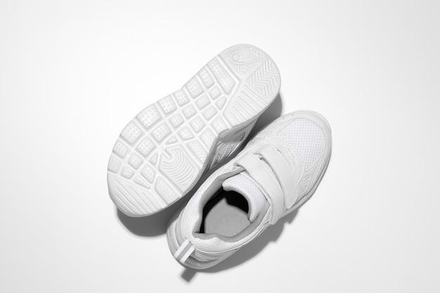 Macro vista dall'alto due scarpe da ginnastica bianche una scarpa da ginnastica si trova la suola con ombre dure isolate su un bianco...