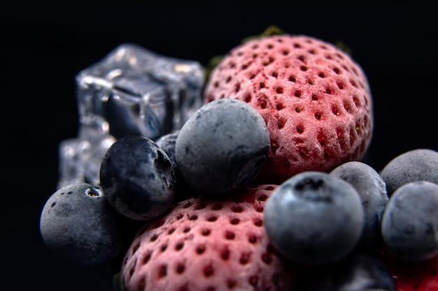 Macro vista delle bacche congelate: fragola, mirtillo con cubetti di ghiaccio