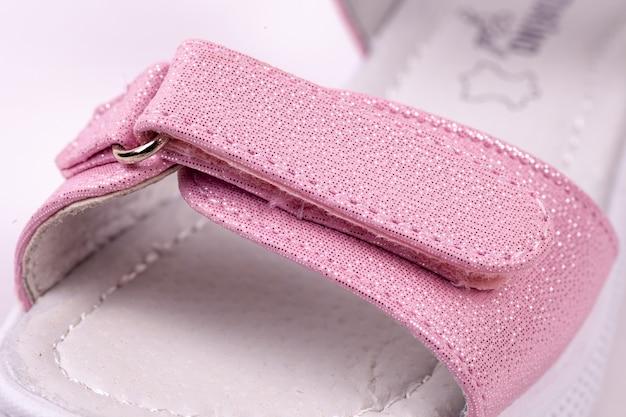 Macro con le calzature casual di estate del sandalo rosa delle ragazze sui precedenti isolati bianchi