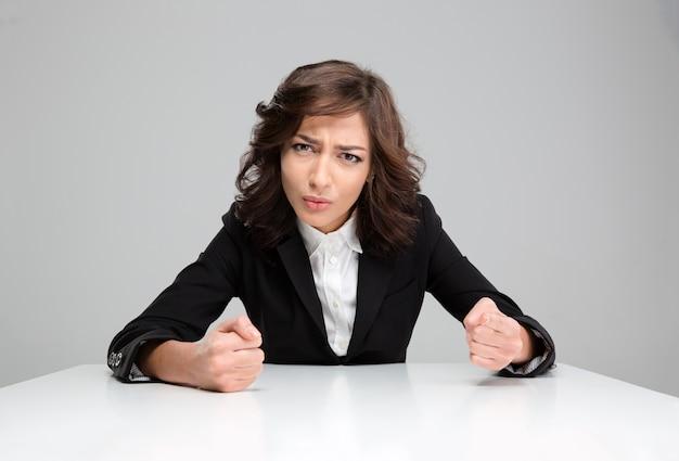 Pazza aggressiva giovane donna riccia infastidita in giacca nera seduta e puntata su di te