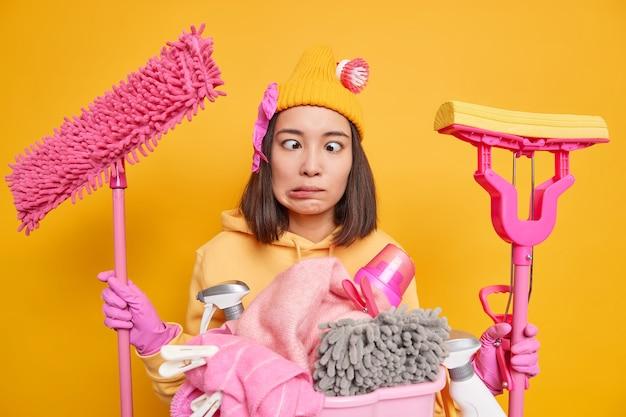 La casalinga asiatica pazza si scherza mentre fa le faccende domestiche tiene due stracci occupati a pulire e fare il bucato incrocia gli occhi indossa guanti di gomma protettivi isolati su sfondo giallo studio