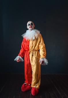 Pagliaccio insanguinato pazzo con trucco in costume di carnevale, maniaco pazzo, mostro spaventoso
