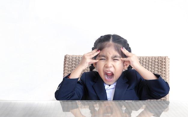 Emozione pazza di azione del bambino asiatico sul tavolo con bianco isolato