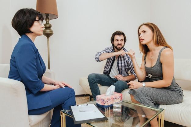 Il pazzo guarda sua moglie che la minaccia. la giovane donna sta guardando il medico e sta parlando con lei. il terapista la ascolta molto attentamente.