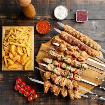 Piatto fatto di spiedini, pollo alla griglia, manzo, carne di maiale con barbecue e salsa tzatziki servito con patatine fritte al buio.