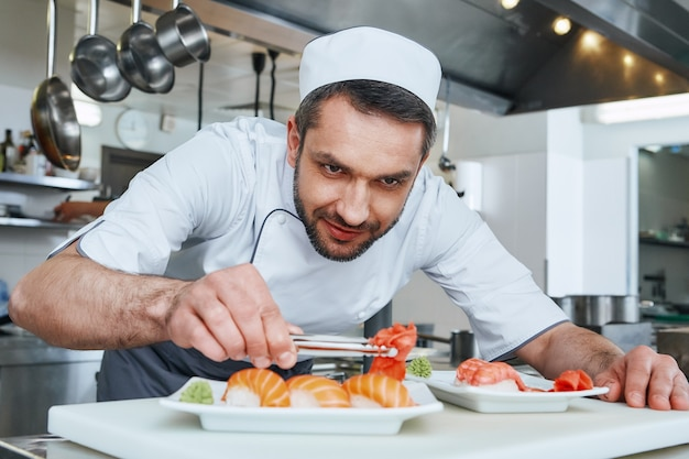 Fatto fresco sempre il maestro di sushi prepara il sushi per servire nella moderna cucina commerciale