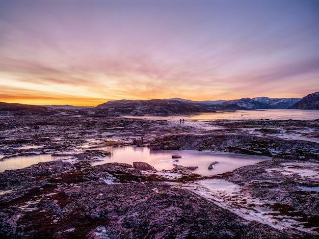 Alba d'inverno magenta. il paesaggio ghiacciato e le montagne del villaggio russo teriberka.