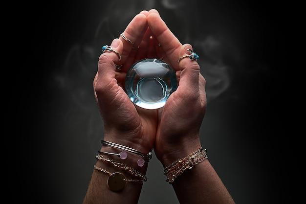 Sfera di cristallo blu magica con fumo nelle mani dell'indovino per la predizione e la divinazione su un muro nero scuro