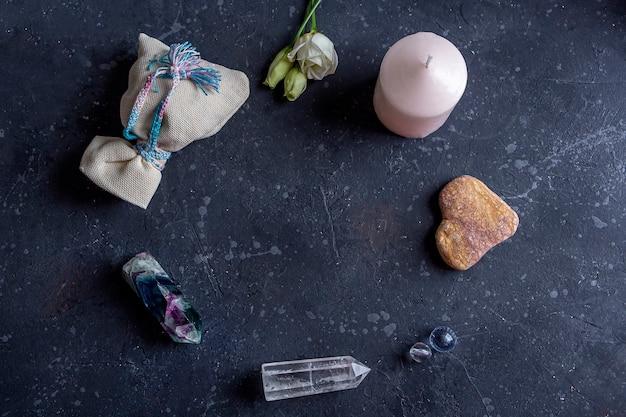 Composizione magica piatta con cristalli di candele rosa borsa pagana e fiori rituali esoterici e pagani stregoneria pratica wiccan o spirituale di guarigione rituale per amore trattamento a base di erbe