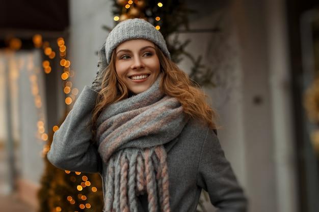 Magico ritratto felice di una giovane e bella donna sorridente in abiti a maglia vintage con un cappello e una sciarpa in vacanza vicino a luci gialle