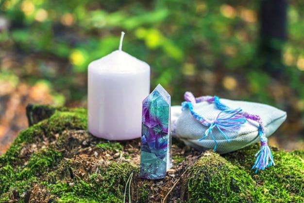 Natura morta magica con fluorite, cristallo di quarzo, candela e borsa con pozione