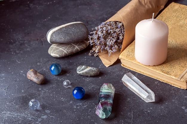 Natura morta magica con fluorite, cristallo di quarzo e candela rosa.