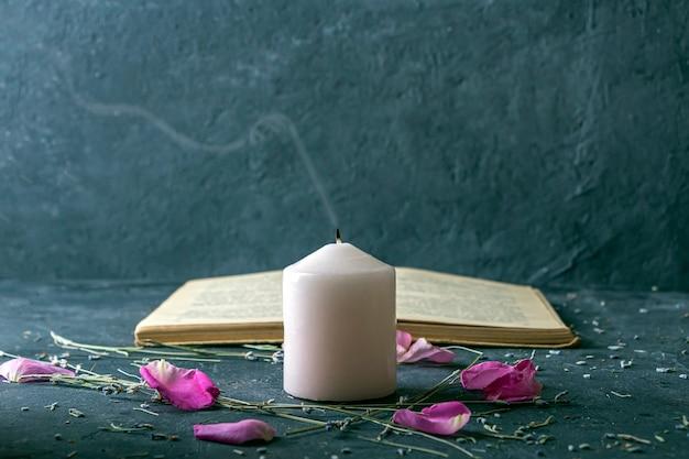 Natura morta magica con candela rosa e vecchio libro di erboristeria.
