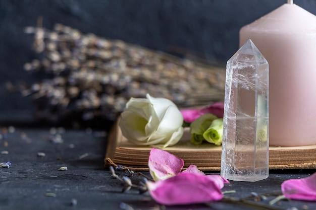Natura morta vintage magica con cristalli, candela rosa, vecchio libro e fiori di rosa