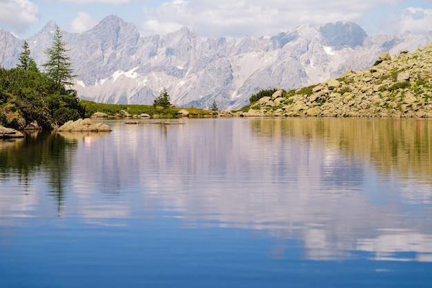 Magico paesaggio idilliaco con il lago nelle montagne delle alpi in europa. sentiero turistico sulle verdi colline delle alpi.