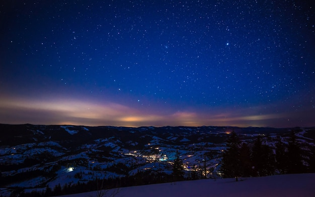 Il magico paesaggio della foresta di conifere che cresce tra le colline in inverno contro un cielo stellato blu e un tramonto cremisi. posto per la pubblicità. posto per il testo