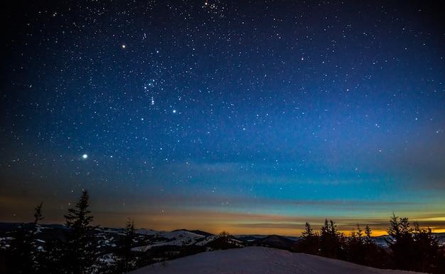 Il magico paesaggio della foresta di conifere che cresce tra le colline in inverno contro un cielo stellato blu e un tramonto cremisi