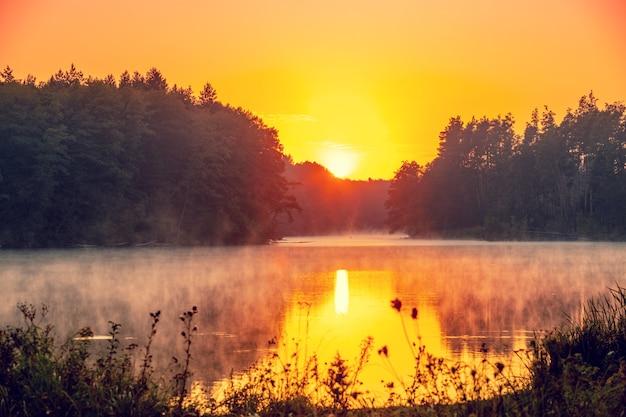 Magica alba sul lago con un bellissimo riflesso sull'acqua. lago sereno nelle prime ore del mattino. paesaggio della natura