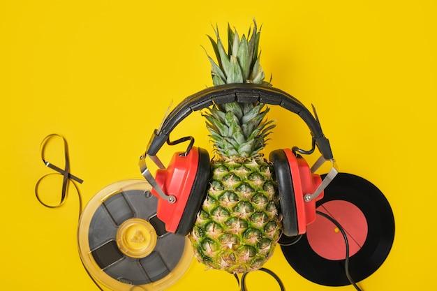 Nastro audio magnetico, vinile e ananas in cuffie retrò rosse su sfondo giallo, vista dall'alto