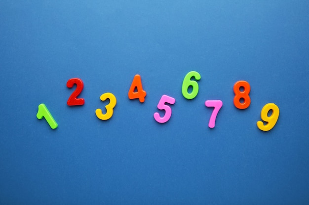 Figure multicolori magnetiche su sfondo blu con spazio di copia. di nuovo a scuola.