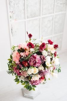 Magnifico mazzo di fiori in vaso bianco.