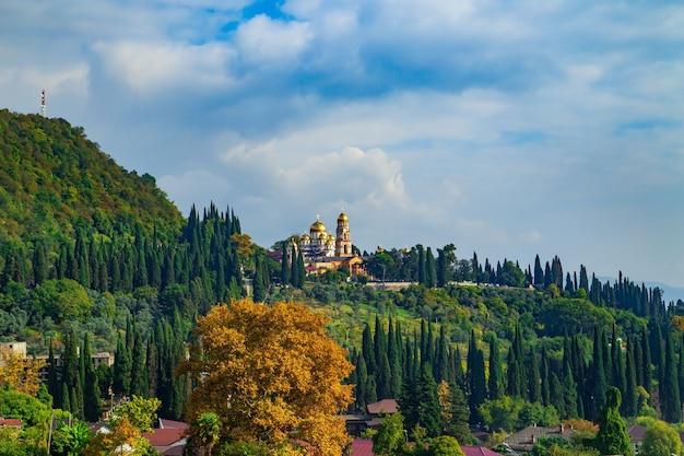 Magnifico nuovo monastero di athos in autunno. giornata di sole, natura luminosa e cielo blu. abkhazia.